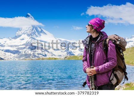 Girl with backpack, in the background mount Matterhorn - Swiss Alps, Europe - stock photo