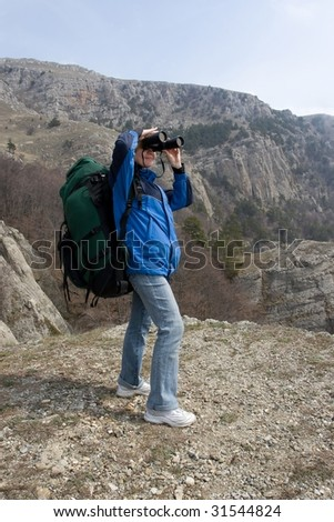 Girl with backpack is using her binocular in high mountains.