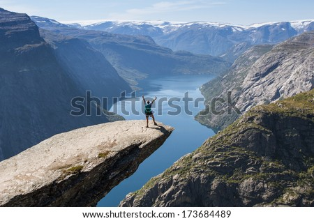 girl with backpack on trolltunga in norway  - stock photo