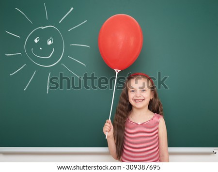 girl with balloon draw sun on school board - stock photo