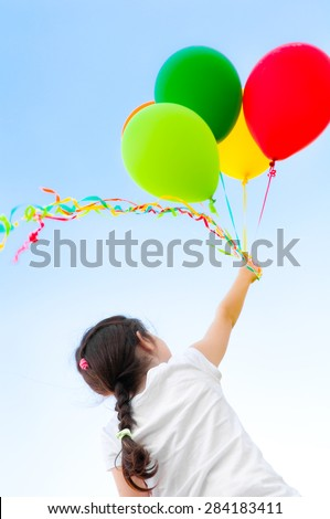 Girl with balloons flying in the sky