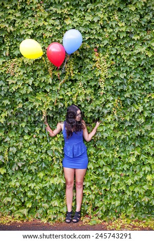 Girl with Balloons in front of wall covered in vine  - stock photo