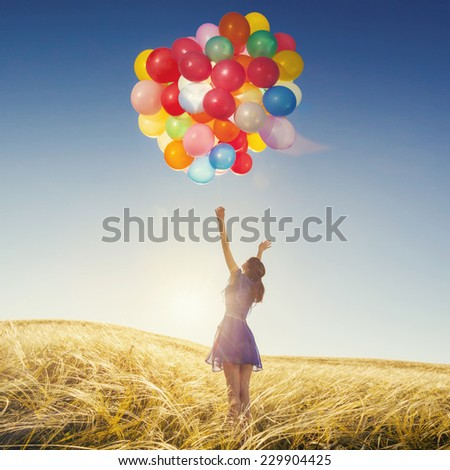 Girl with balloons in nature. Happy woman in a field at sunset. Holidays. - stock photo