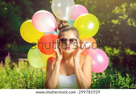 Girl with balloons in nature making facial expressions - stock photo