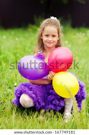 girl with balloons on the grass - stock photo