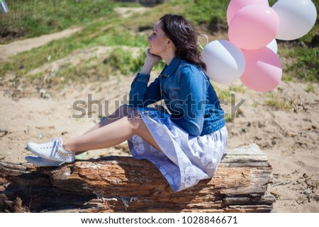 girl with balloons sitting on a stump