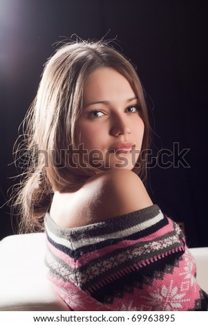 girl with bare shoulders looks into the camera