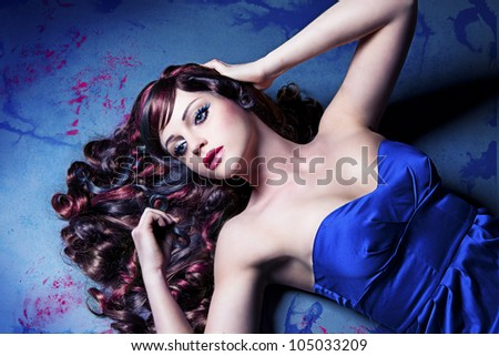 girl with beautiful colored curly hair lying on a painted floor like a doll - stock photo