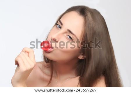 girl with beautiful hair sucks a lollipop.  - stock photo