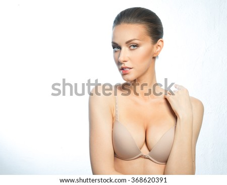 Girl with beautiful, large breasts, in a beige bra, with a beautiful face.