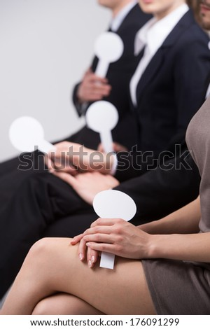 girl with beautiful legs sitting and voting. group of people holding cards with numbers - stock photo