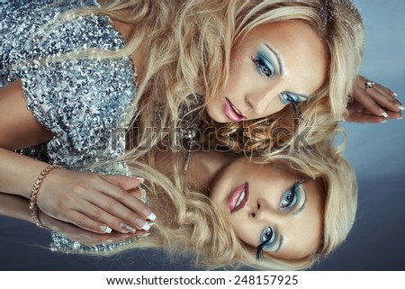 Girl with beautiful make-up posing looking in the mirror. - stock photo