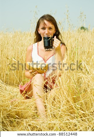 Girl  with beer and bread  at wheat field - stock photo