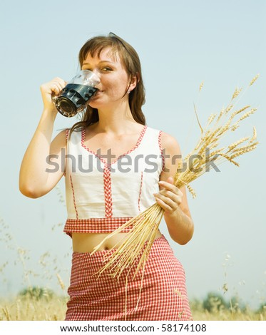 Girl  with beer and wheat ears  at cereals field - stock photo