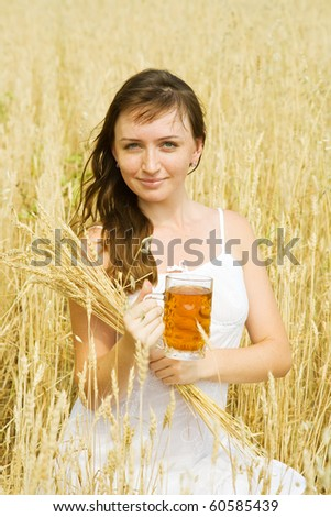 Girl  with beer at cereals field in summer - stock photo