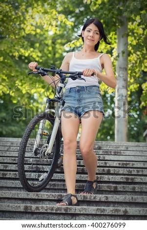 girl with bike walking on steps - stock photo