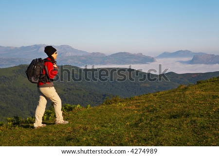 Girl with black backpack walking on the meadow - stock photo