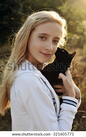 Girl with black cat. Teenage girl holding a cat in her arms, who kisses her on the cheek - stock photo