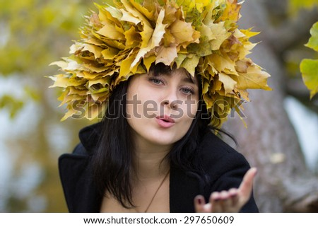 girl with black hair wearing a wreath of leaves