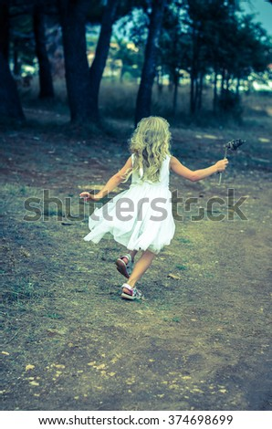 girl with blond hair running in forrest