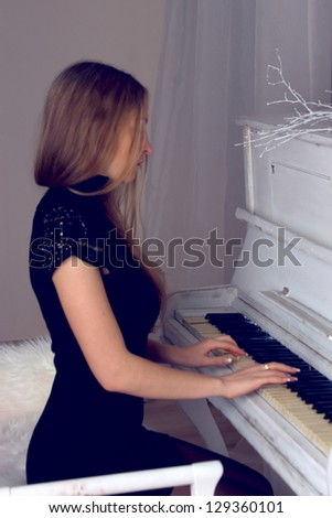 girl with blond long  hair in  dress playing white piano - stock photo