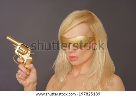 Girl With Blonde Hair wearing Gold shades Holding a Gun. - stock photo