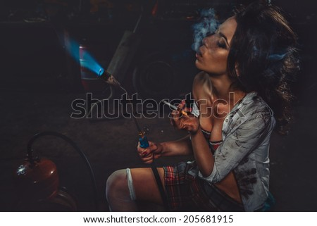 Girl with blowpipe smoking in a garage  - stock photo