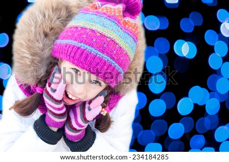Girl with blue Christmas tree lights behind - stock photo