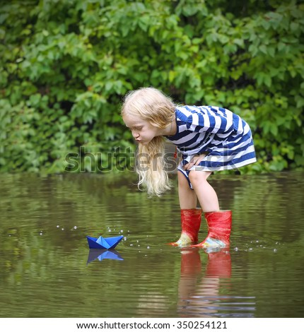 Girl with blue paper boat in a puddle after the rain, summer - stock photo