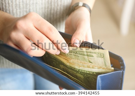 Girl with blue wallet full of money - stock photo
