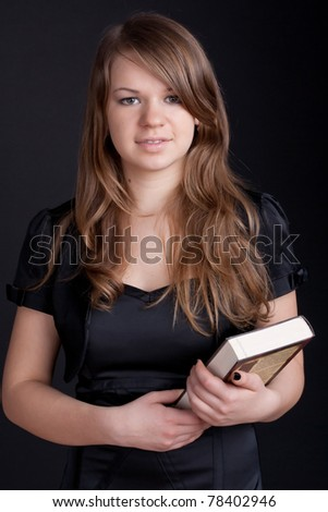 Girl with book in hand on a black background - stock photo