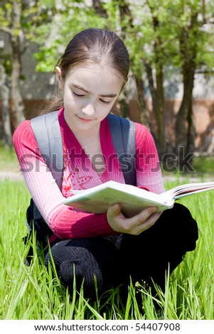 Girl with book. Studying on nature. - stock photo