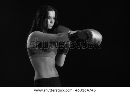 girl with boxing gloves on a black background