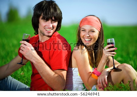 Girl with boy and with wineglasses on grass - stock photo