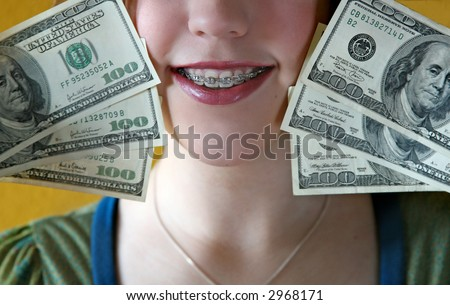 girl with braces holding cash - stock photo