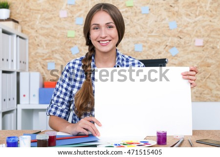Girl with braided hair in checkered shirt is holding large blank piece of paper. Concept of advertising. Mock up
