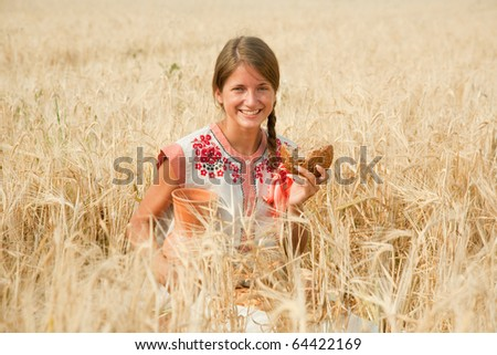 Girl with bread and jug of milk  at rye field - stock photo