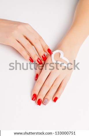 girl with bright red nail polish on the nails and cream heart on hand