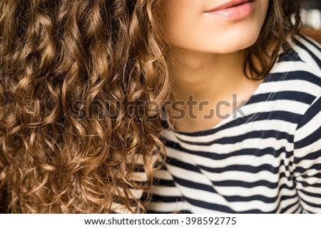 Girl with brown curly hair in a striped T-shirt close-up - stock photo