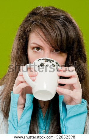 Girl with brown hair drinking coffee - stock photo
