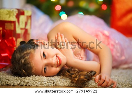girl with brown hair lying on the carpet. Christmas tree in the background. smiles - stock photo