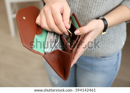 Girl with brown wallet full of money - stock photo