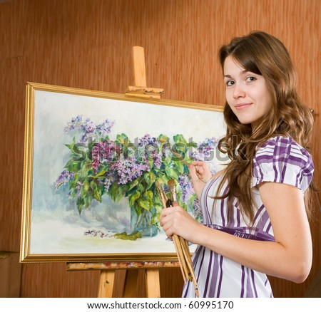 Girl with brushes near  easel with picture of flowers in interior - stock photo