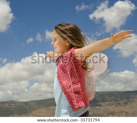 girl with butterfly wings and cloudy sky - stock photo