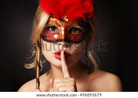 Girl with carnival mask. Beautiful young woman with finger on her red lips showing hush. Halloween. Masquerade