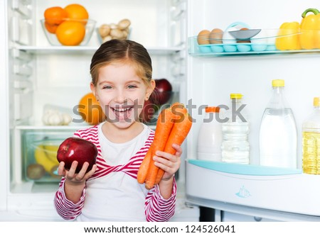 girl with carrots on background refrigerator - stock photo