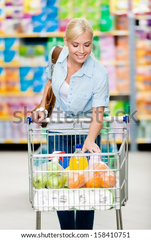 Girl with cart full of food in the shop. Concept of consumerism, retail and purchase