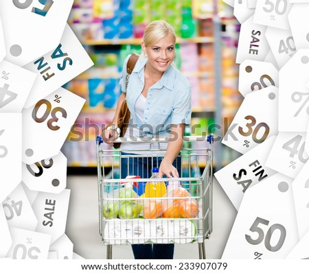 Girl with cart full of food in the shopping center. Sale coupons background. Concept of consumerism, retail and purchase - stock photo