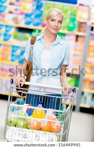 Girl with cart full of food in the store. Concept of consumerism, retail and purchase - stock photo