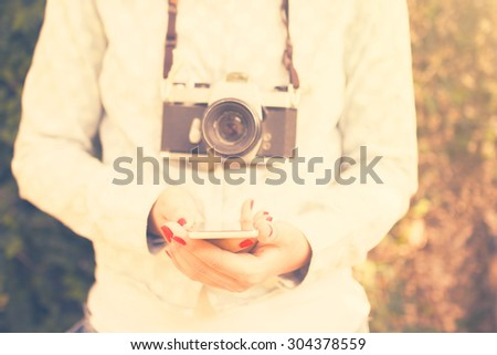 Girl with cell phone and old camera, vintage color effect - stock photo
